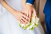 A Newly Weding Couple Place Their Hands On A Wedding Bouquet Showing Off Their Wedding Rings. poster