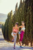 Stretching before jogging. Young Woman runner. jogging outdoors. poster