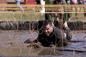 POCONO MANOR, PA - APR 29: A man crawls through water under electrified wires at Tough Mudder on Apr