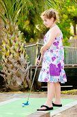 Menina jogando golfe mini curso de putt putt