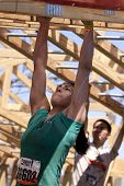 POCONO MANOR, PA - APR 29: A woman moves hand-over-hand through an obstacle at Tough Mudder on April