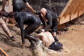 POCONO MANOR, PA - APR 28: Participants are helped from the water during the Tough Mudder event on A