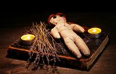 Voodoo doll girl on a wooden table in the candlelight
