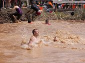 POCONO MANOR, PA - APR 28: A man splashes into water after jumping off an obstacle at Tough Mudder o