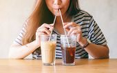 Closeup Image Of A Beautiful Asian Woman Drinking Two Glasses Of Iced Coffee With Stainless Steel St poster