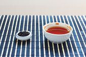 Cup of tea and jar of tea leaves on bamboo table cloth