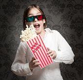 little girl wearing 3D glasses and eating popcorn