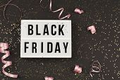 Black Friday Sale Text On White Lightbox, Golden Stars And Holiday Ribbon Around On Black Background poster