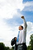 stock photo of woohoo  - Portrait of happy man standing outside in rural environment with his arm raised upwards - JPG