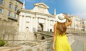 Beautiful Young Woman With Hat Climbs Towards Porta San Giacomo Gate In Bergamo Upper City On Sunny  poster