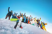 Big Group Of Happy Skiers And Snowboarders With Raised Arms Stands On Snowdrift At Ski Resort. Ski A poster