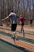 POCONO MANOR, PA - APR 29: Participants walk across a narrow beam over water at Tough Mudder on Apri
