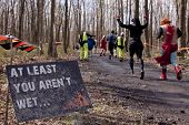 POCONO MANOR, PA - APR 28: Participants run past a sign that reads At Least You Aren't Wet at Tough Mudder on April 28, 2012 in Pocono Manor, Pennsylvania. British Royal troops designed the course.