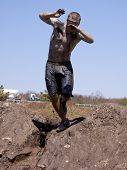 POCONO MANOR, PA - APR 29: A man loses his balance on the banks of a mud pit at Tough Mudder on Apri