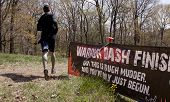 POCONO MANOR, PA - APR 28: A man runs past a sign that reads Warrior Dash Finish at Tough Mudder on April 28, 2012 in Pocono Manor, Pennsylvania. British Royal troops designed the course.