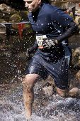 POCONO MANOR, PA - APR 28: A man runs through a flowing cold water creek at Tough Mudder on April 28, 2012 in Pocono Manor, Pennsylvania. The course is designed by British Royal troops.