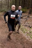 POCONO MANOR, PA - APR 28: Two men run on a trail through the woods at Tough Mudder on April 28, 2012 in Pocono Manor, Pennsylvania. The course is designed by British Royal troops.