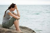 stock photo of suicide  - Upset and depressed woman sitting by the ocean crying with her head in her hand - JPG