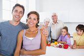 Mutter und Vater von Küchentheke mit Familie dahinter stehend