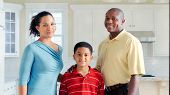 African American Family Stands In Kitchen Smiling