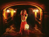 pic of dungeon  - Romantic brunette holding a lantern in a dark dungeon - JPG