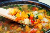 Vegetable Soup With Carrots, Paprika, Potatoes, Onions And Parsley With A Wooden Spoon