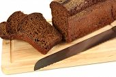 Sliced black bread and knife on wooden board close up