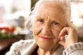 stock photo of stroll  - Portrait of the smiling elderly woman sitting outdoor - JPG
