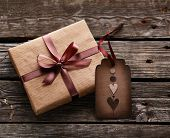 Vintage gift box with gift tag on old wooden background.