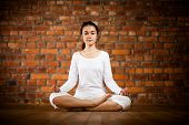 stock photo of pranayama  - Girl exercising yoga against brick wall - JPG