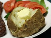 foto of baked potato  - close up of a baked potato and butter on a plate  - JPG