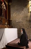 17th century church interior and a nun in prayer at the altar