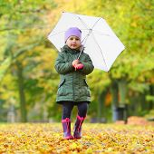 Little girl with umbrella walking in the city park. Rainy day concept.
