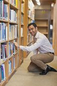 Young attractive man cowering in front of bookshelves smiling friendly at camera