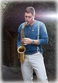 Young saxophonist plays on his sax with bright emotions in the street. Serbia.