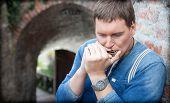 Young harmonica player plays on the street of Novi Sad, Serbia.