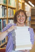 Happy female librarian holding a pile of books in a library smiling at camera