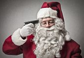 portrait of Santa Claus pointing a gun on his head