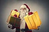 Santa Claus holding many Christmas gifts