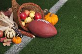 stock photo of cornucopia  - A football with a cornucopia on a grass field with white stripe - JPG
