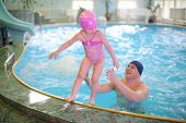 Little girl jumping into the pool, her father in the pool catches her