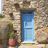 blue door and flowerpot in a mediterranean island