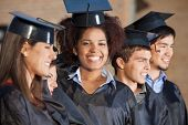 Portrait of happy young woman with friends in a row on graduation day at college