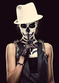 foto of hush  - Woman with skeleton face art making a hush gesture over black background - JPG