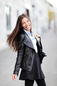 City girl - modern urban woman smiling happy from the heart. Female fashion wearing black leather ja