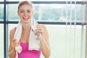 Portrait of a cheerful young woman with towel around neck holding water bottle in fitness studio
