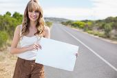 Smiling pretty woman holding sign while hitchhiking on a deserted road in summertime