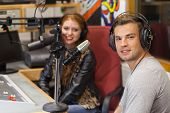 Attractive cheerful radio host interviewing a guest in studio at college