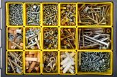 Screws, Bolts, Wall Plugs, Nuts And Other Carpenter Stuff In A Yellow Plastic Toolbox, Top View