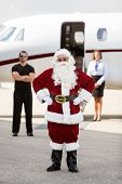 Full length portrait of Santa with hands on hip standing against bodyguard; airhostess and private jet